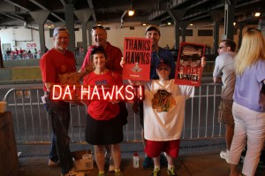 """Optiva Signs celebrates the Blackhawks' Stanley Cup win by having fans pose with a portable, battery-powered """"DA' HAWKS"""" SpellBrite sign."""