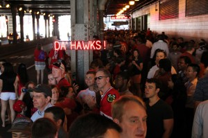 "Optiva Signs celebrates the Blackhawks' Stanley Cup win by having fans pose with a portable, battery-powered ""DA' HAWKS"" SpellBrite sign."